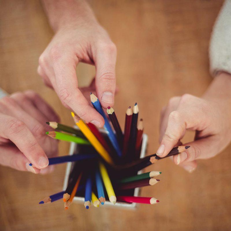 creative-team-choosing-different-coloured-pencils-PMSUVPX.jpg